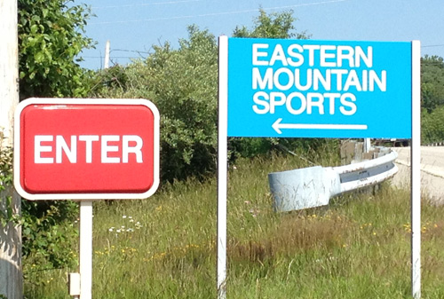 Eastern Mountain Sports logo rebrand on parking lot sign.